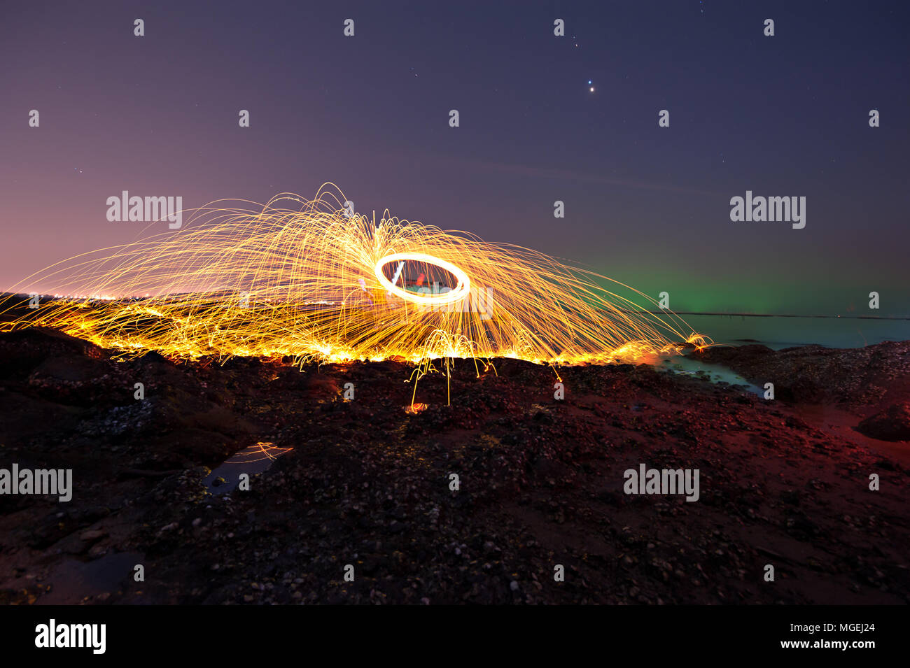 Showers of hot glowing sparks from spinning steel wool on the beach Stock Photo