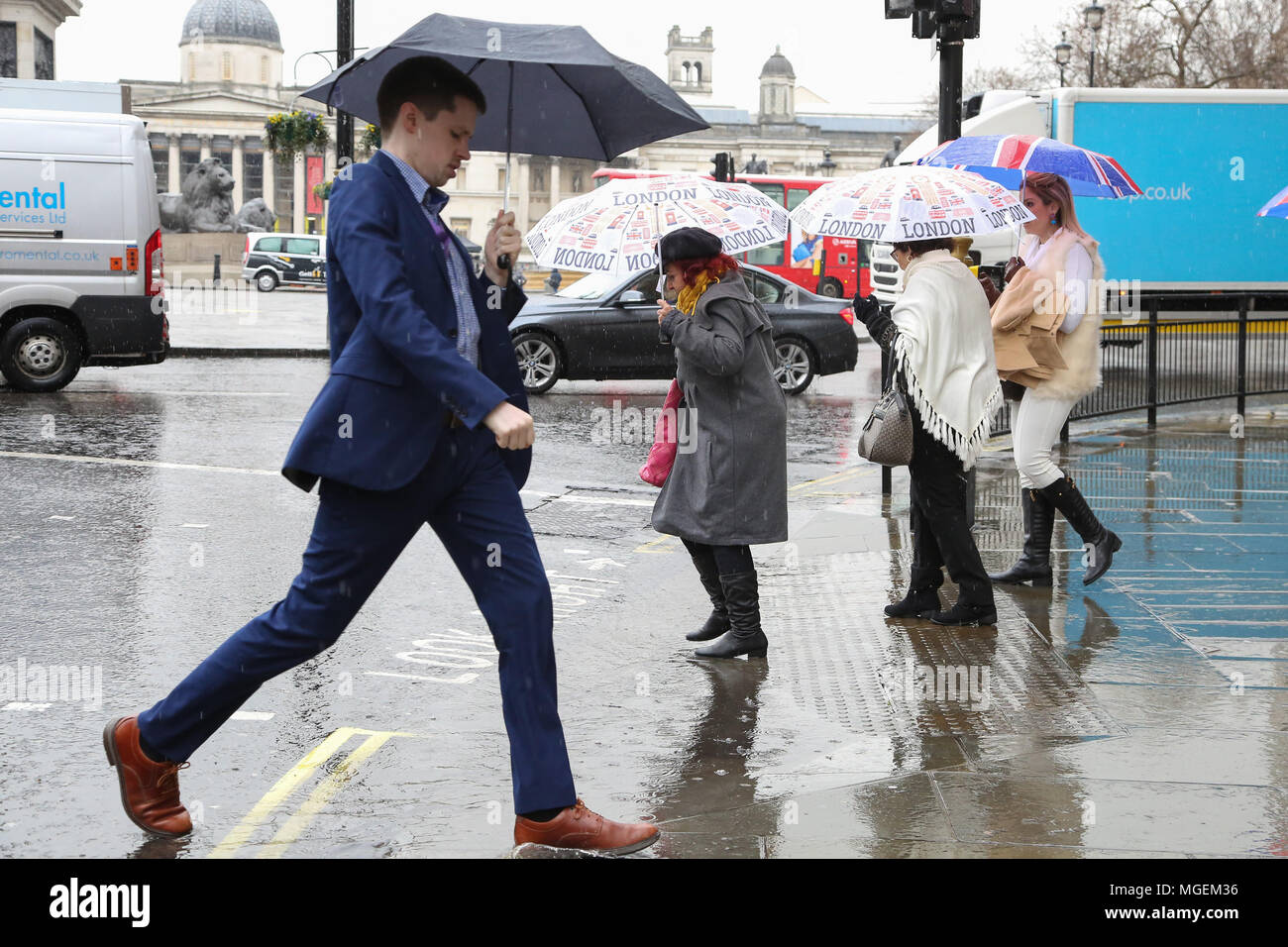 Tourists with umbrellas and wearing rain ponchos in the rain, avoiding puddle of rainwater near Trafalgar Square  Featuring: Atmosphere, View Where: London, United Kingdom When: 28 Mar 2018 Credit: Dinendra Haria/WENN - Stock Image
