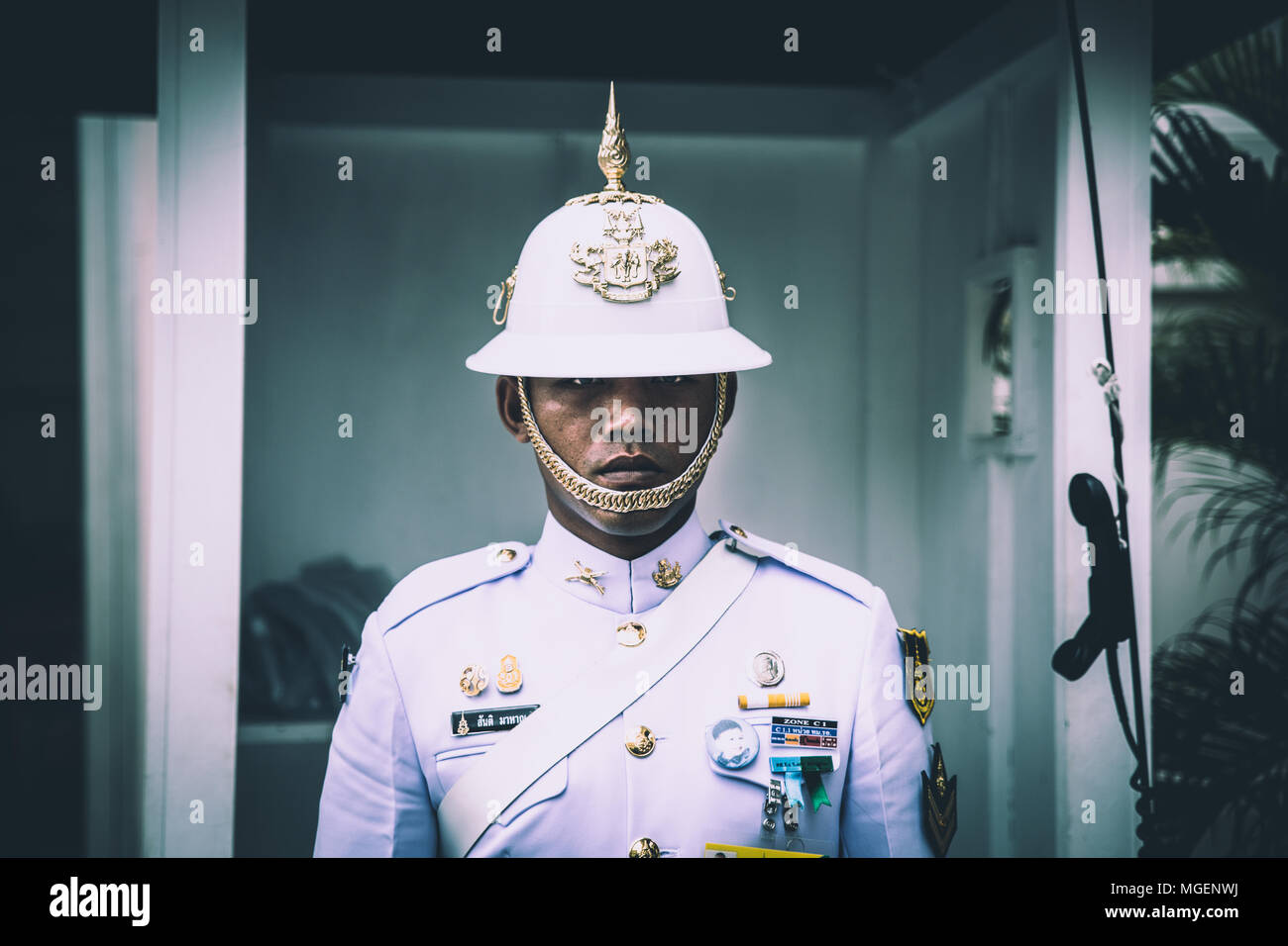 A guard with Asian traits dressed in white with a decorated helm controls impassive tourists outside the temple of Wat Pho in Bangkok Stock Photo