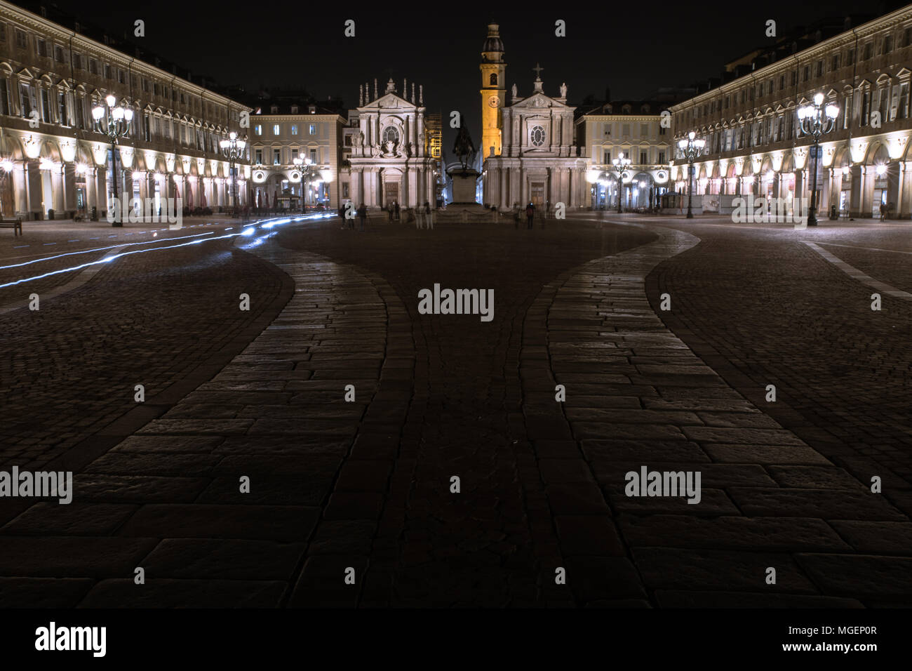 One of the main squares of Turin, Piazza San Carlo, photographed at night while the headlights of the bikes whiz past the historical monuments Stock Photo