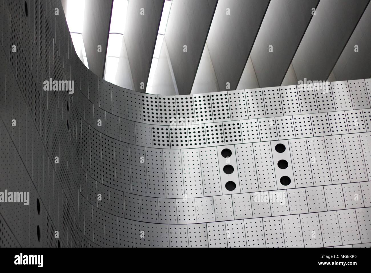 Photograph of a wall made of perforated metal panels with holes of different sizes - Stock Image
