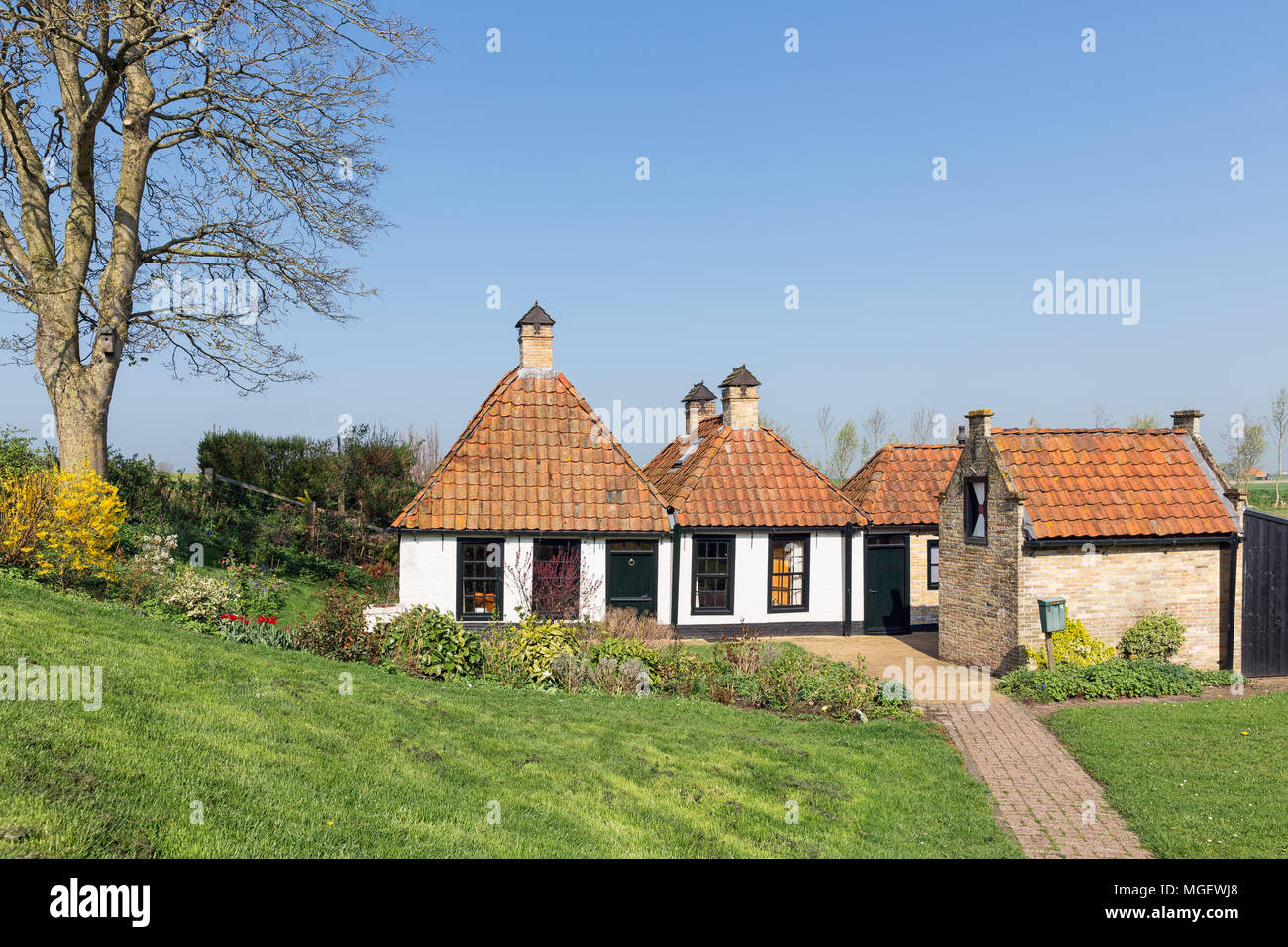 Tradtional Dutch houses near dike for ptotection to the sea - Stock Image