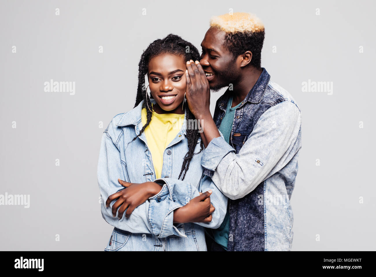 Portrait of a surprised young afro american couple telling secrets isolated - Stock Image