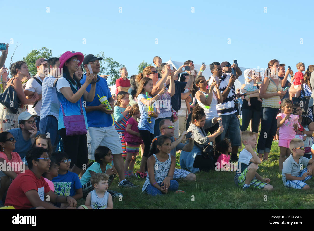 A crowd of onlookers photographing a balloon launch with a variety of handheld cameras,phones and tablets - Stock Image