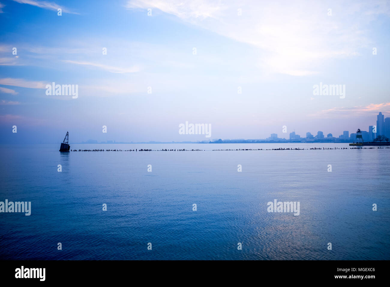 Cool blue minimalist Chicago skyline landscape viewed over Lake Michigan with a pier and navigation beacon in the foreground and silhouetted city on t Stock Photo