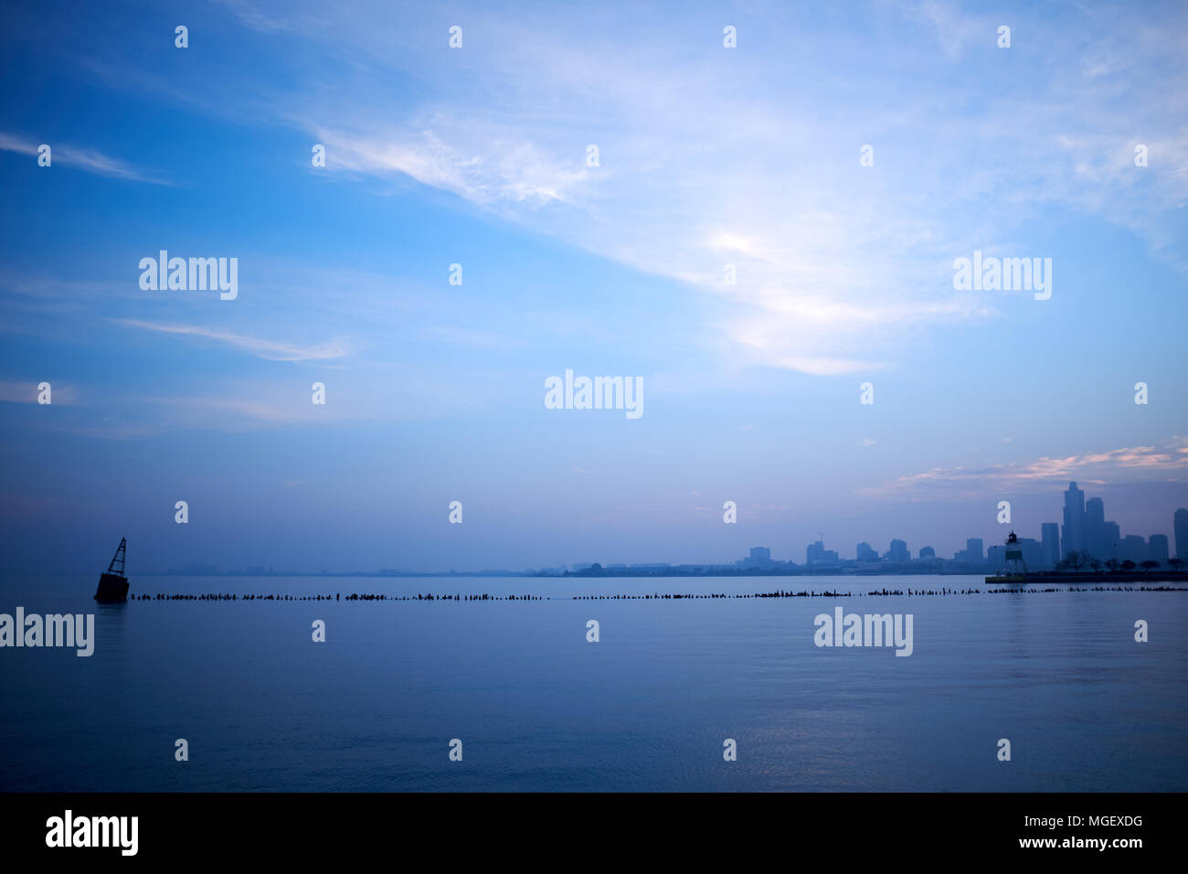 Minimalist blue landscape over Lake Michigan with a breakwater or pier in the foreground and silhouetted Chicago cityscape on the horizon at dusk Stock Photo