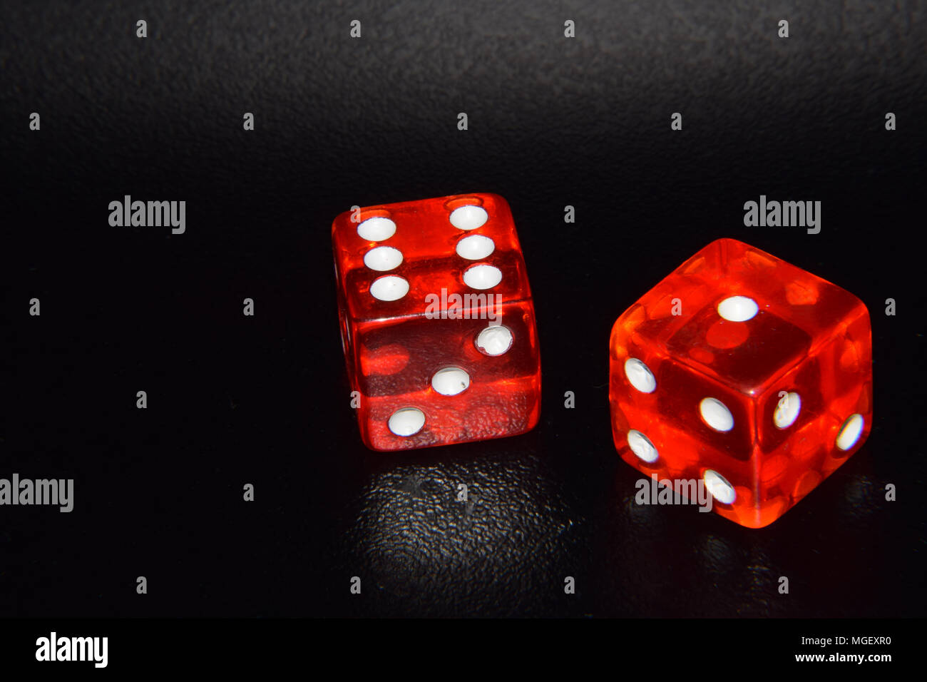 Red luminescent casino gambling dice on black reflecting background Stock Photo