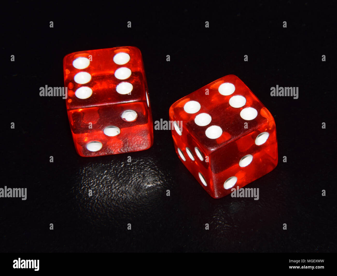 Red luminescent casino gambling dice on black background - double six Stock Photo