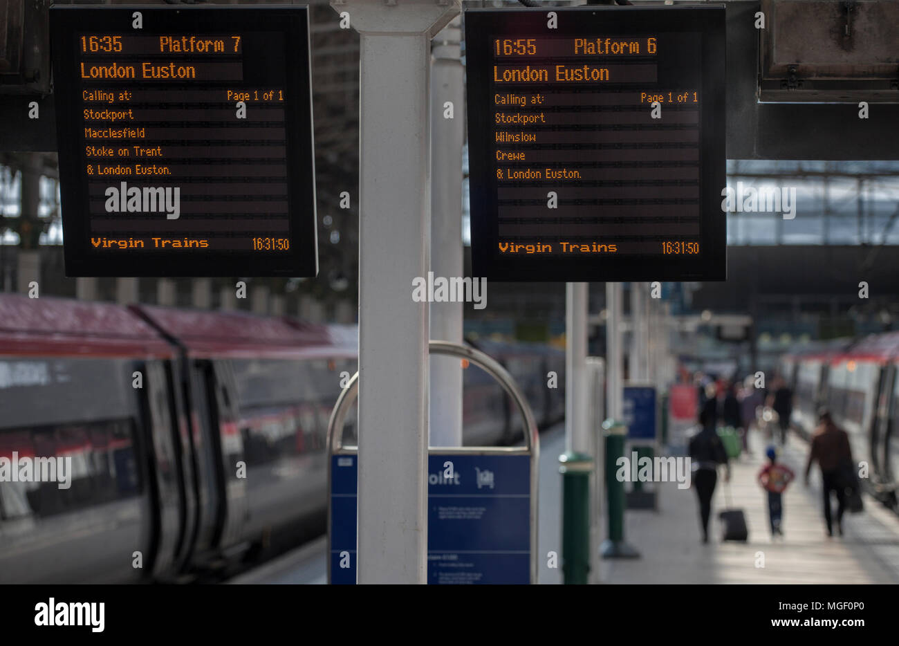 Information screens at Manchester Piccadilly railway station showing the next virgin train to London Euston - Stock Image