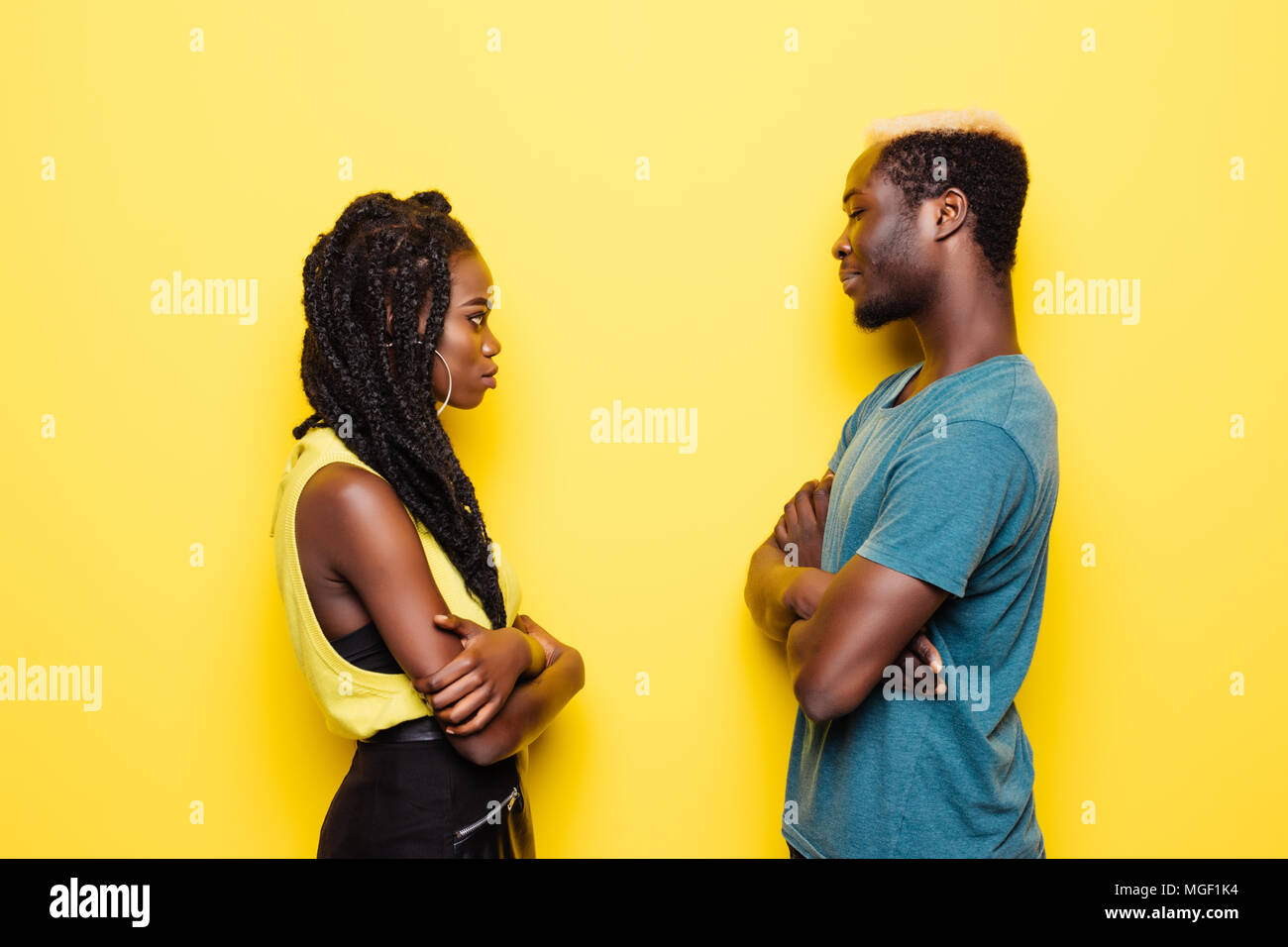 Young afro american couple offended standing face to face isolated on yellow - Stock Image