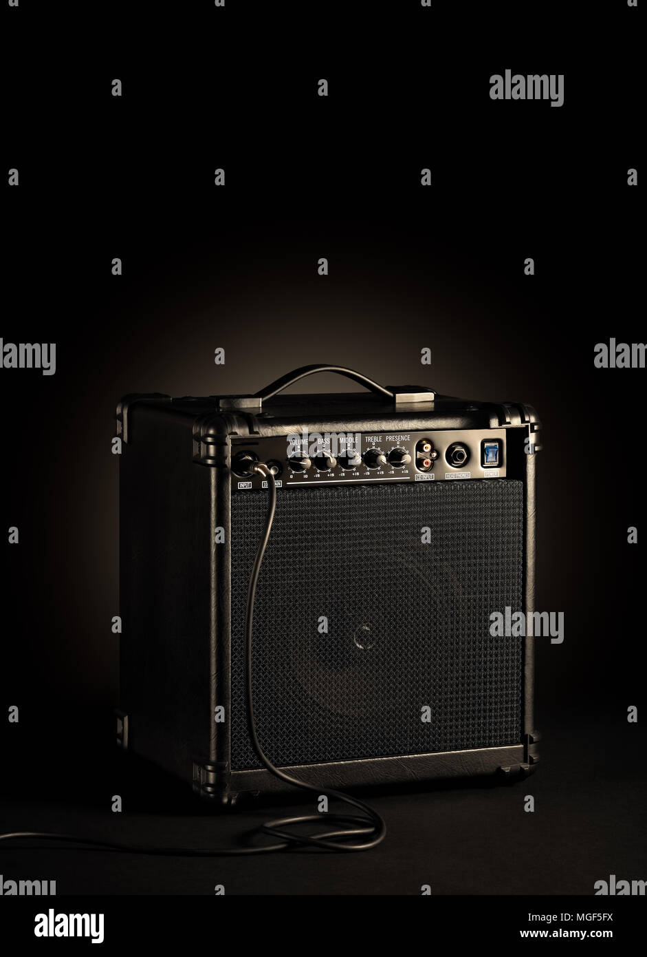 Black bass guitar amplifier whit a cord plugged in on black background Stock Photo