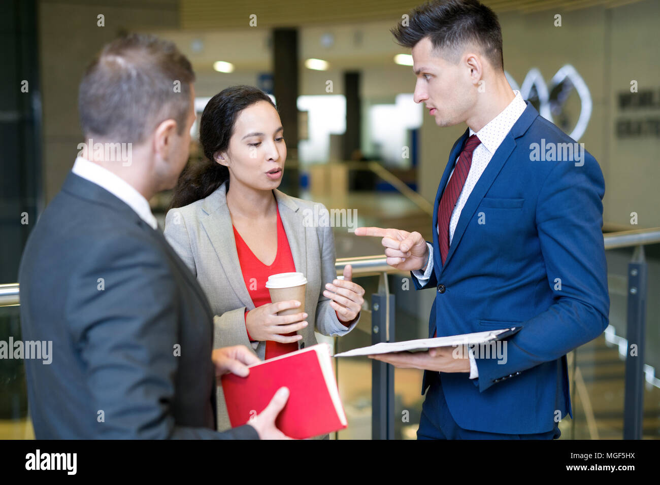 Serious confident mixed race lady proving her opinion while talking to young entrepreneurs after business conference - Stock Image