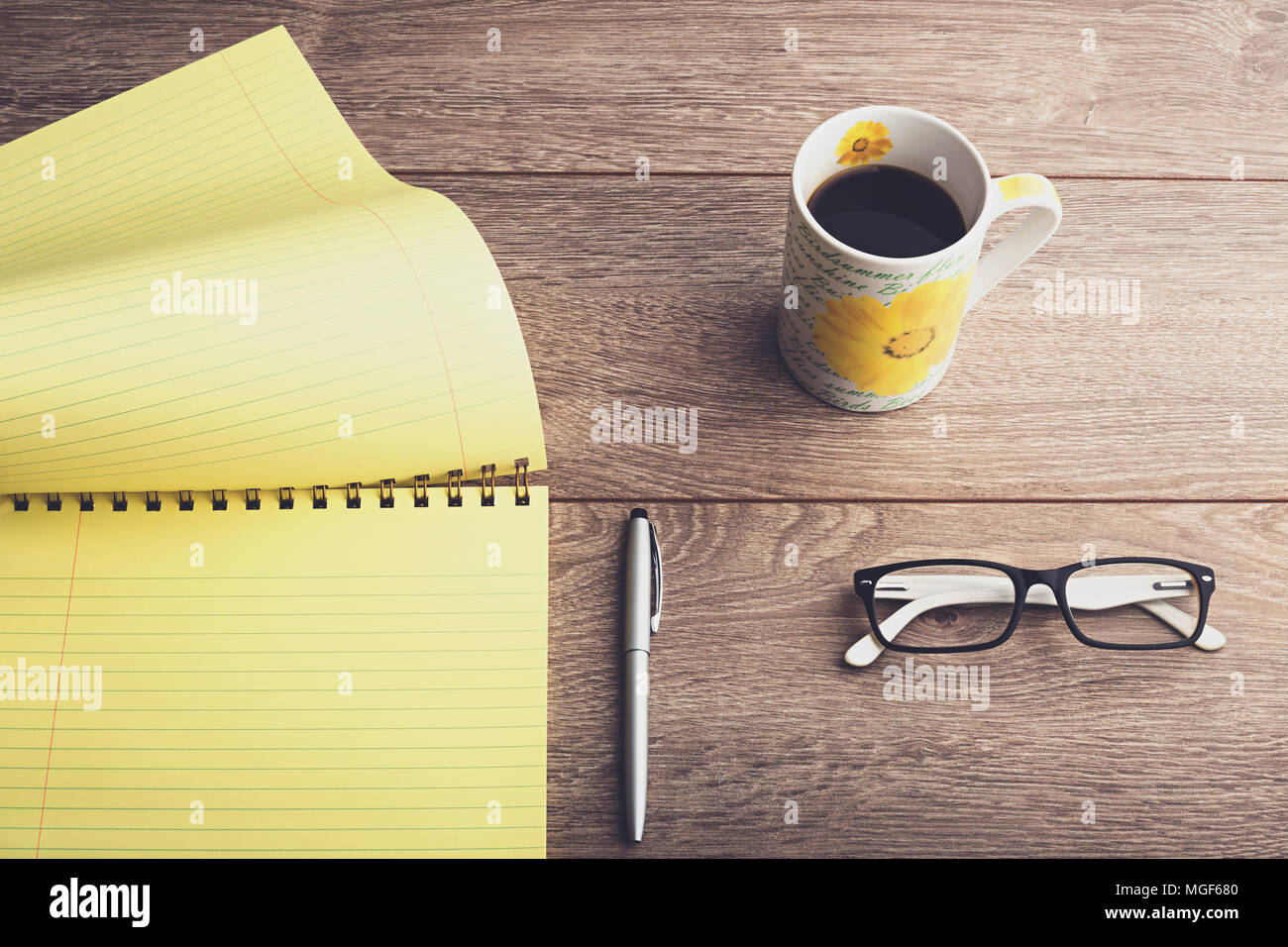 Business desktop. Coffee mug, eyeglasses, pen and yellow notepad on wooden table. Top down view. - Stock Image
