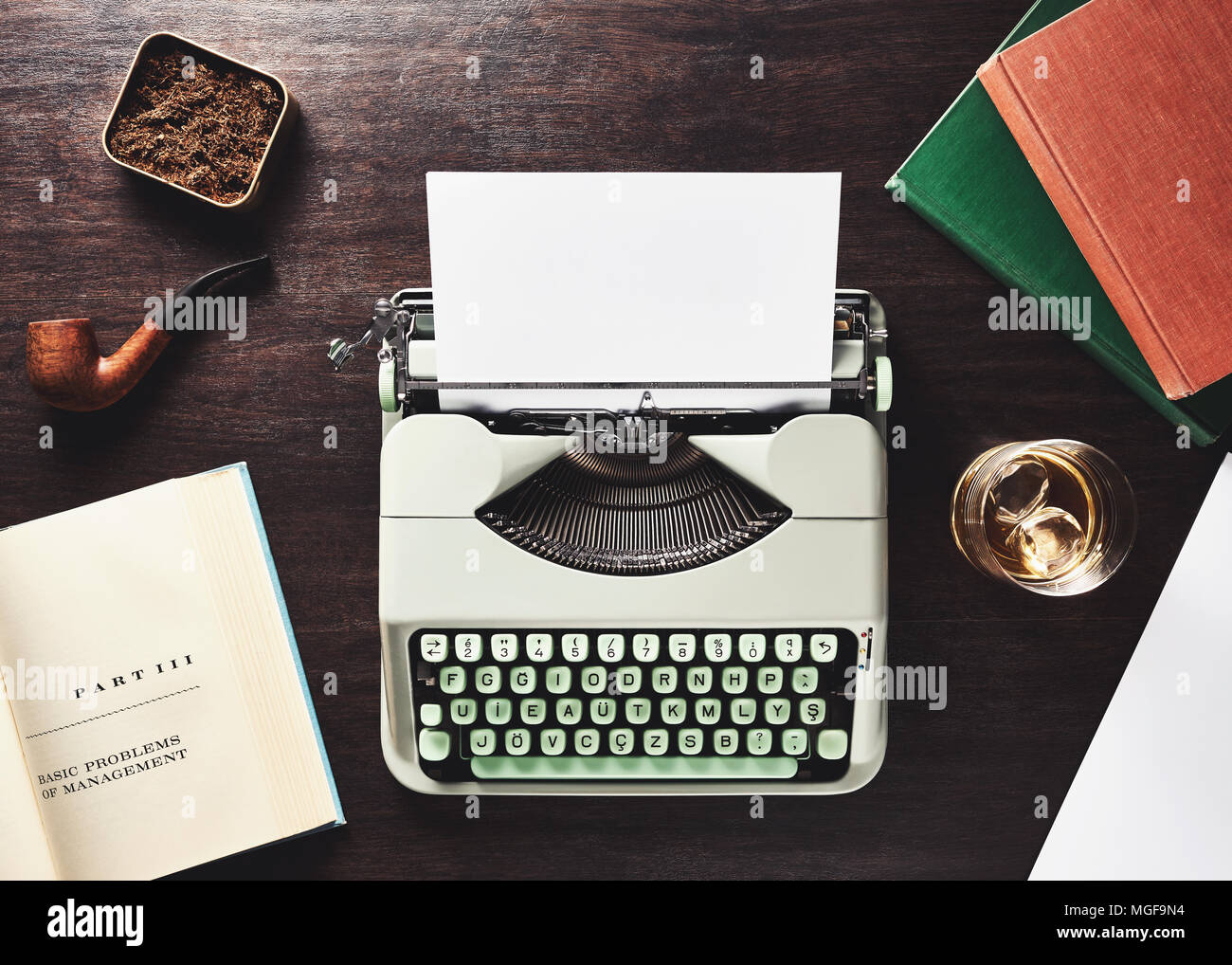Business management problem solving. Vintage f type typewriter, blank paper, pipe, old books, tobacco box and a glass of whiskey on a wooden table - Stock Image