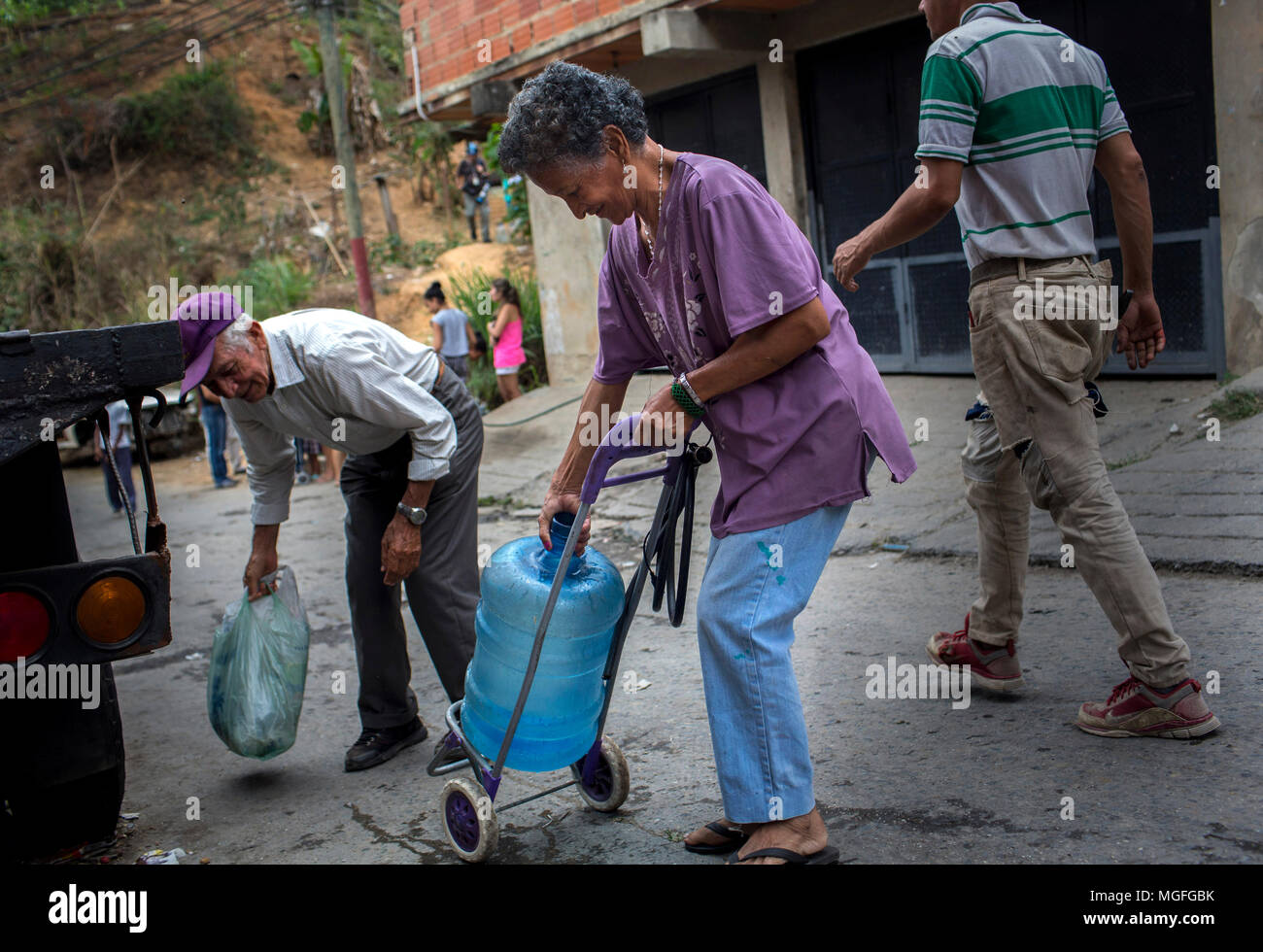 27 April 2018, Venezuela, Caracas: An elderly woman carrying a water jug on an old shopping cart through the Las Minas quarter as she looks for a source of water. The supply of drinking water was interrupted 20 days ago in this quarter. Numerous people are protesting in several cities in the country. The protests were summoned due to problems with supply through public companies. Photo: Manu Quintero/dpa - Stock Image