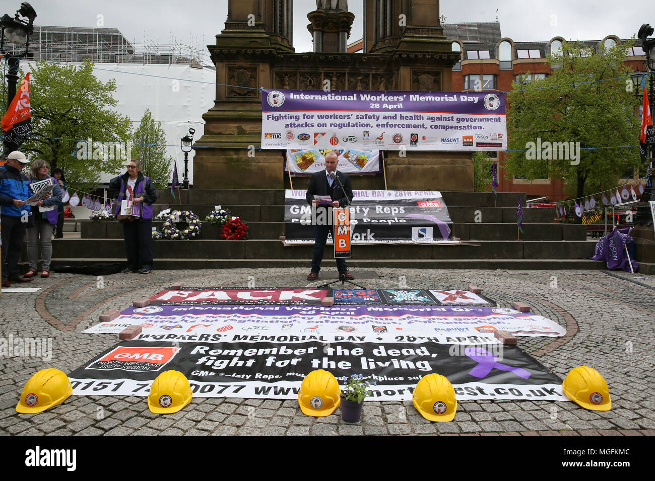Manchester, UK, 28 April 2018. A banner which reads 'Remember the dead, fight for the living' on the ground next to fire fighters helmets on International Workers Memorial Day, Albert Square, Manchester , 28th April, 2018 (C)Barbara Cook/Alamy Live News - Stock Image