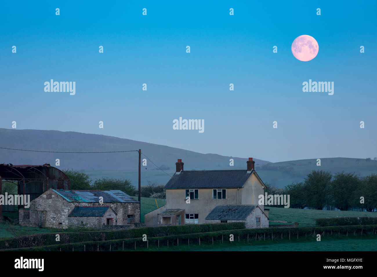 A full moon descending over the Clwydian Range or Clwydian Hills and a rural farm near to the village of Rhes-y-Cae early morning, Flintshire, Wales, UK - Stock Image