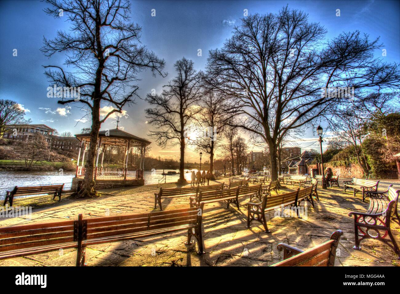 City of Chester, England. Artistic silhouetted view of the empty benches and the Victorian bandstand on the Groves, by the River Dee. - Stock Image
