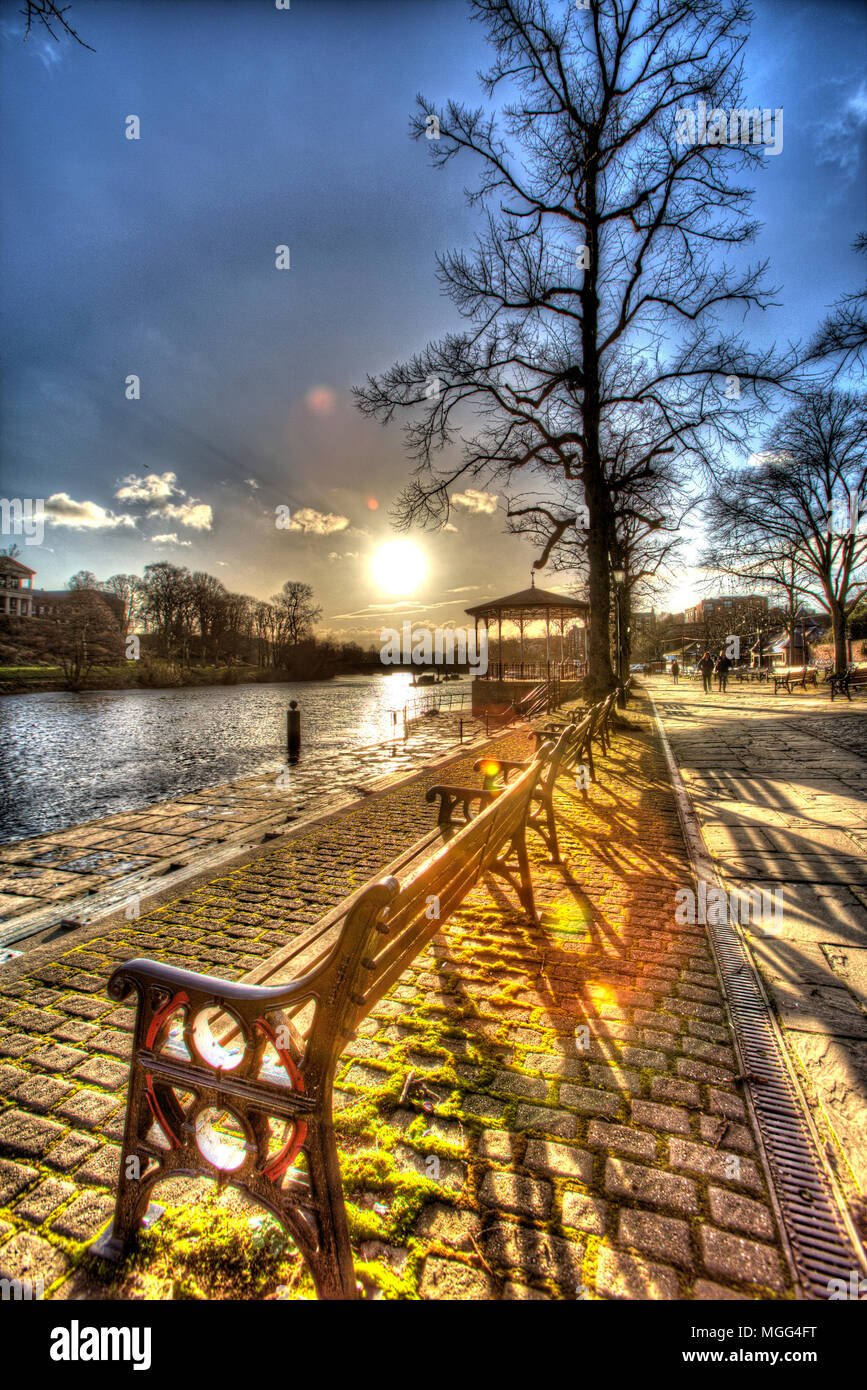 City of Chester, England. Artistic silhouetted view of the empty benches and the Victorian bandstand on the Groves, by the River Dee. Stock Photo