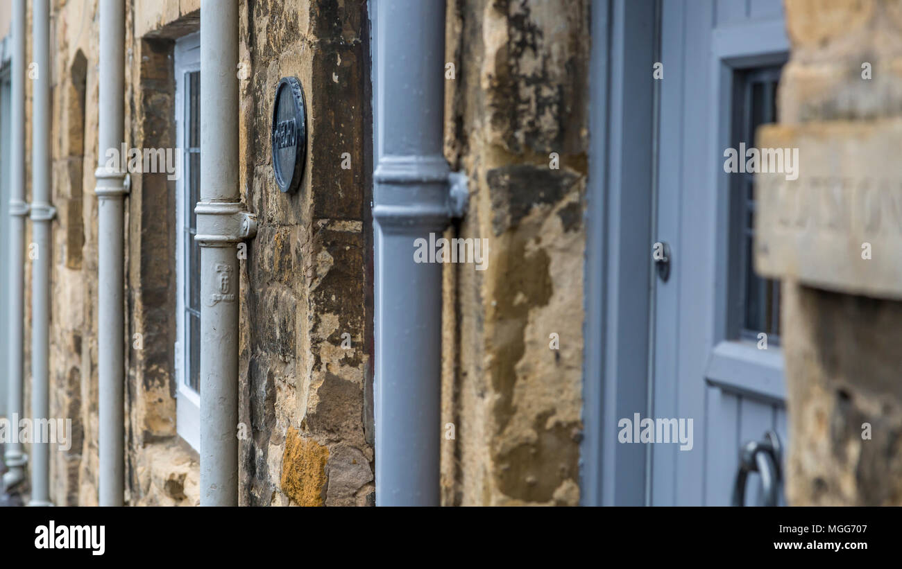 Cast iron water downpipes line up agaist the limestone walls of  terraced cottages in the Cotswold's market town of Chipping Campden Stock Photo