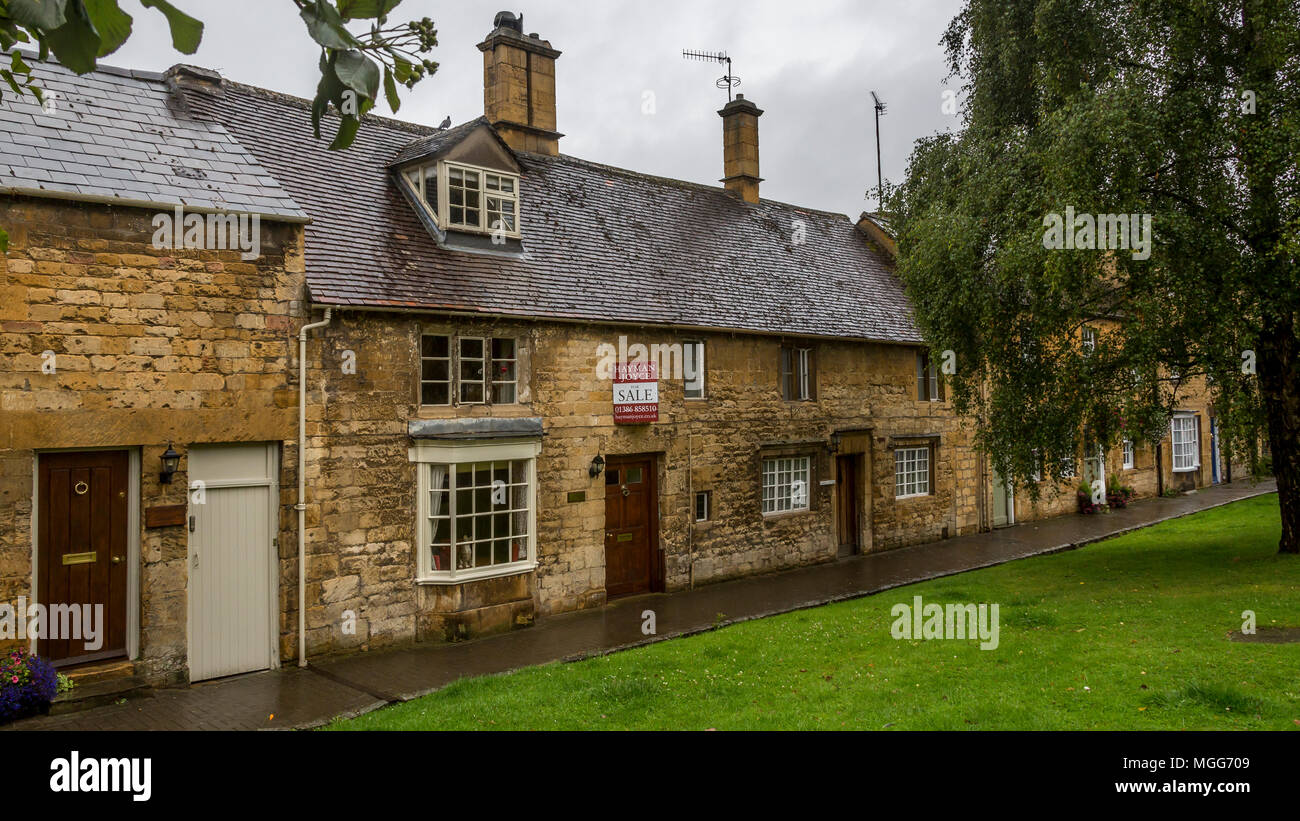 Cotswold limestone adorns the facade of these elegant terraced cottages in the picturesque market town high street of Chipping Campden-one is for sale Stock Photo