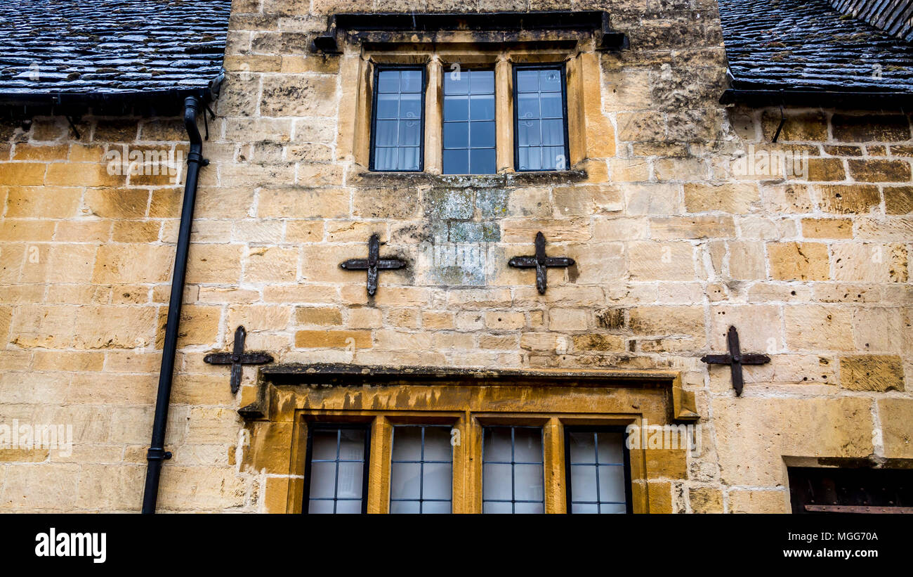 Cotswold limestone is kept in place by four tie plates on the facade of this terraced cottage in the market town high street of Chipping Campden Stock Photo