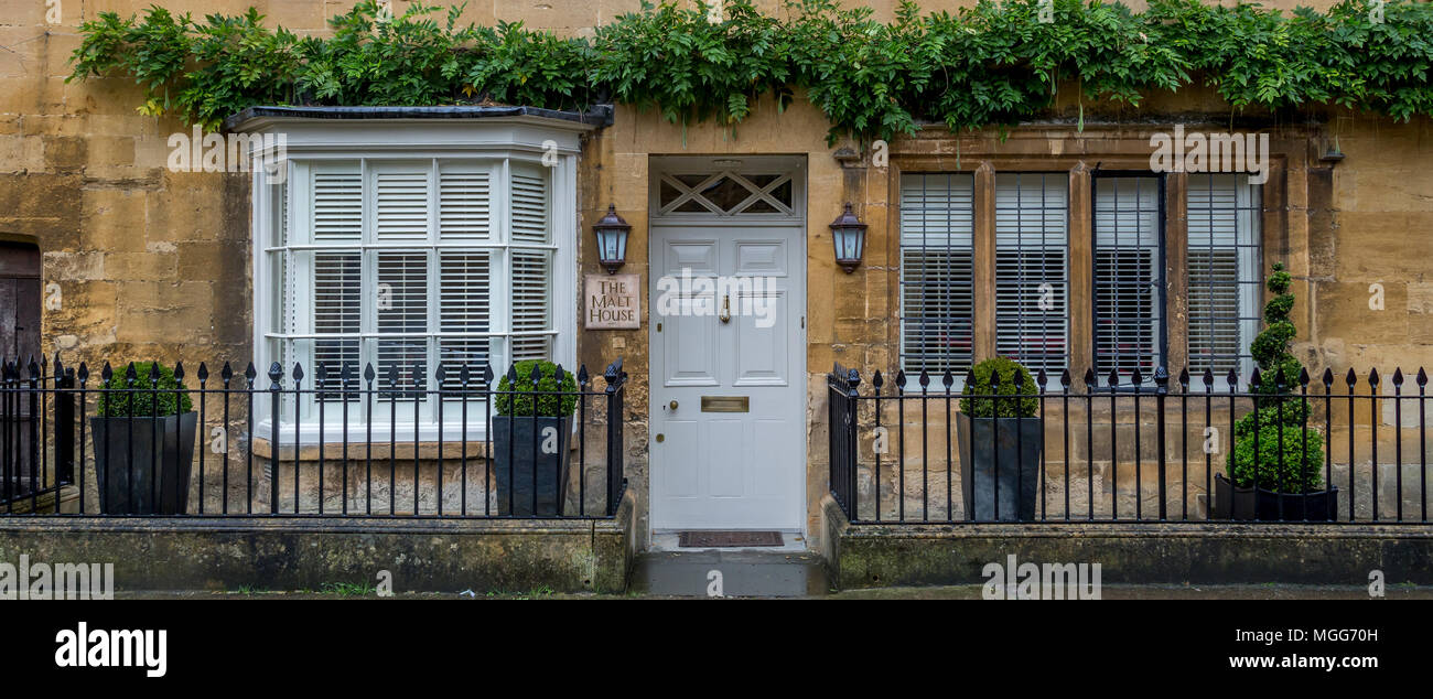 Cotswold limestone adorns the facade of this elegant double fronted terraced house in the picturesque market town high street of Chipping Campden - Stock Image