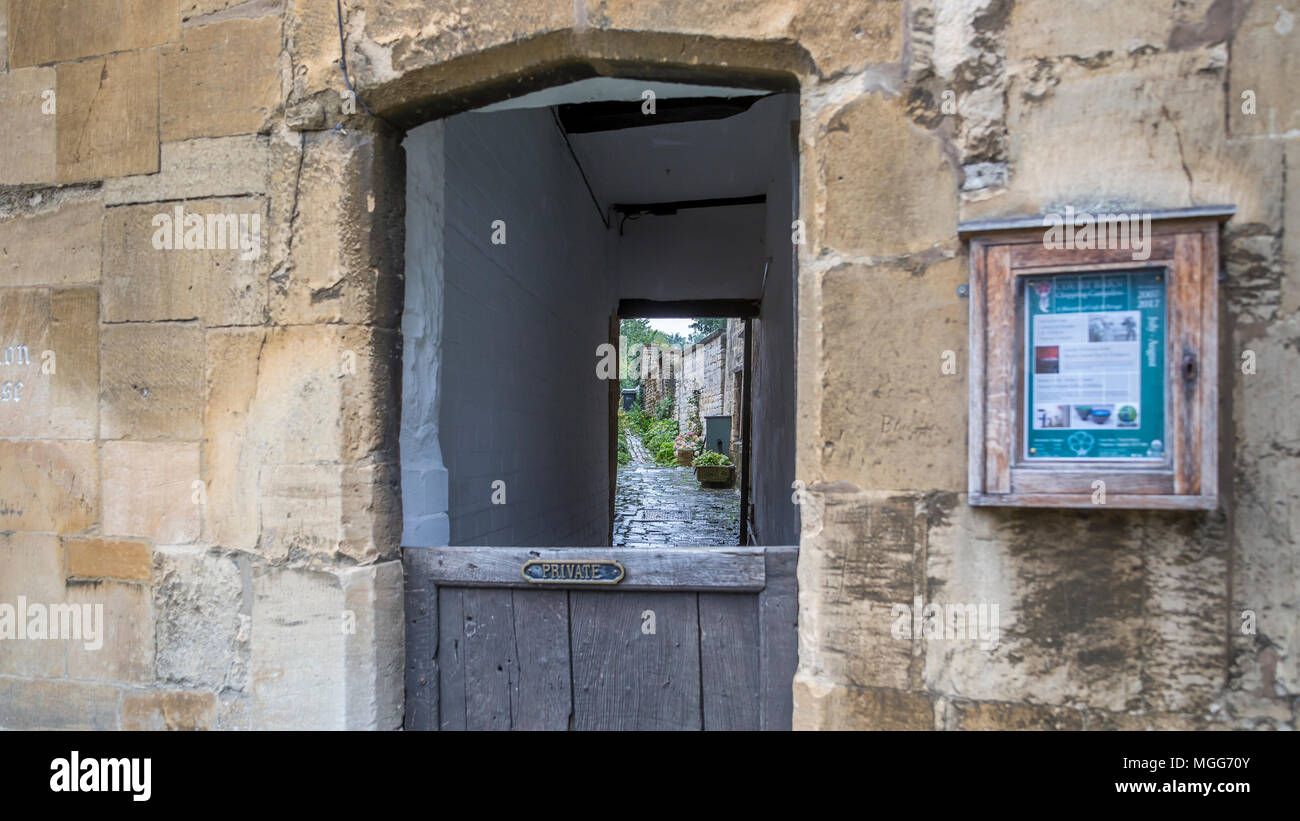 Cotswold limestone surrounds a half doored arched alleyway between terraced houses in the picturesque market town high street of Chipping Campden Stock Photo