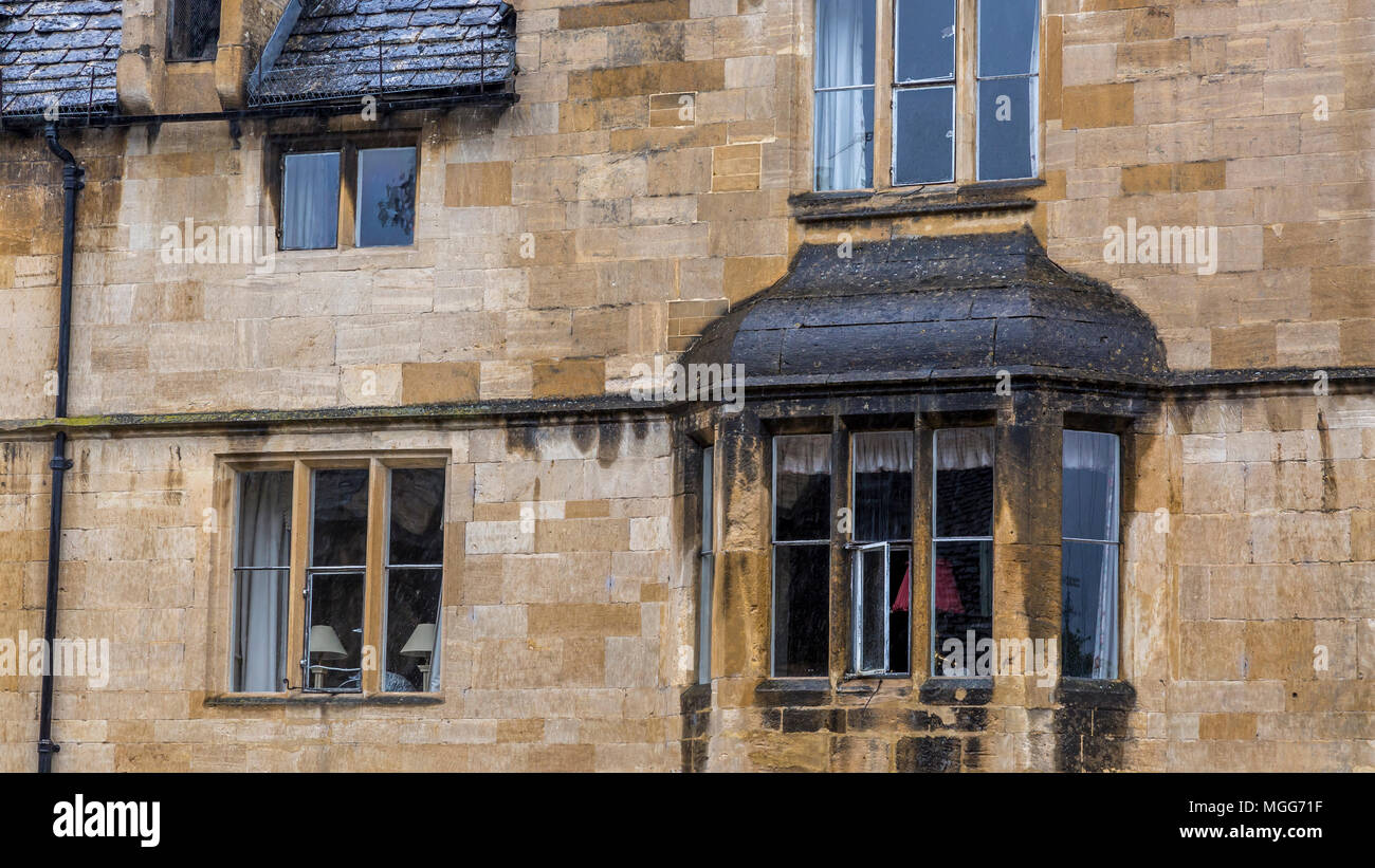 Cotswold limestone adorns the facade and ornate bay of this elegant terraced house in the picturesque market town high street of Chipping Campden Stock Photo