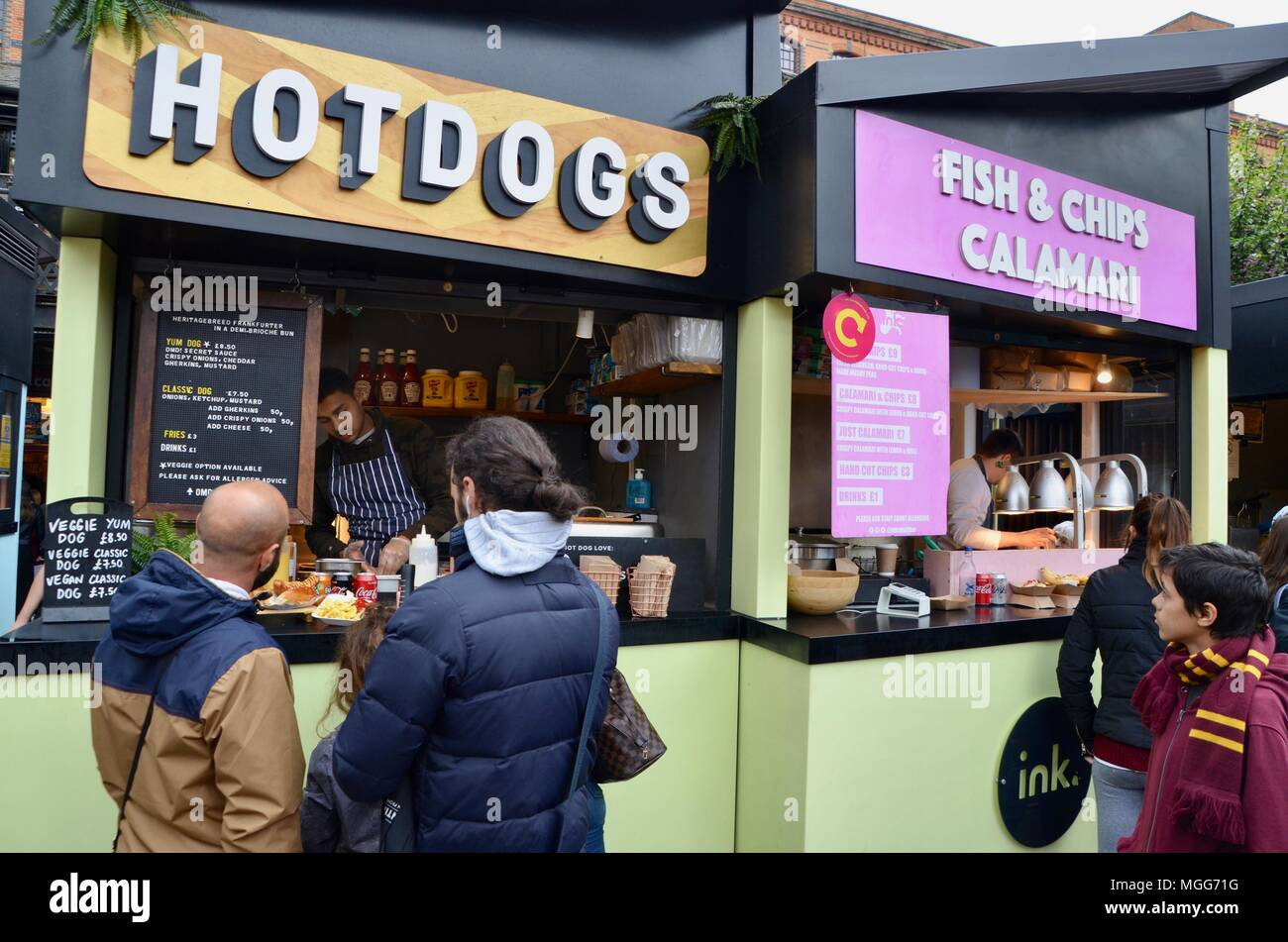 street style food stalls at kerb camden market the stables london UK selling hotdogs fish and chips curries colombian indian and more with tourists - Stock Image