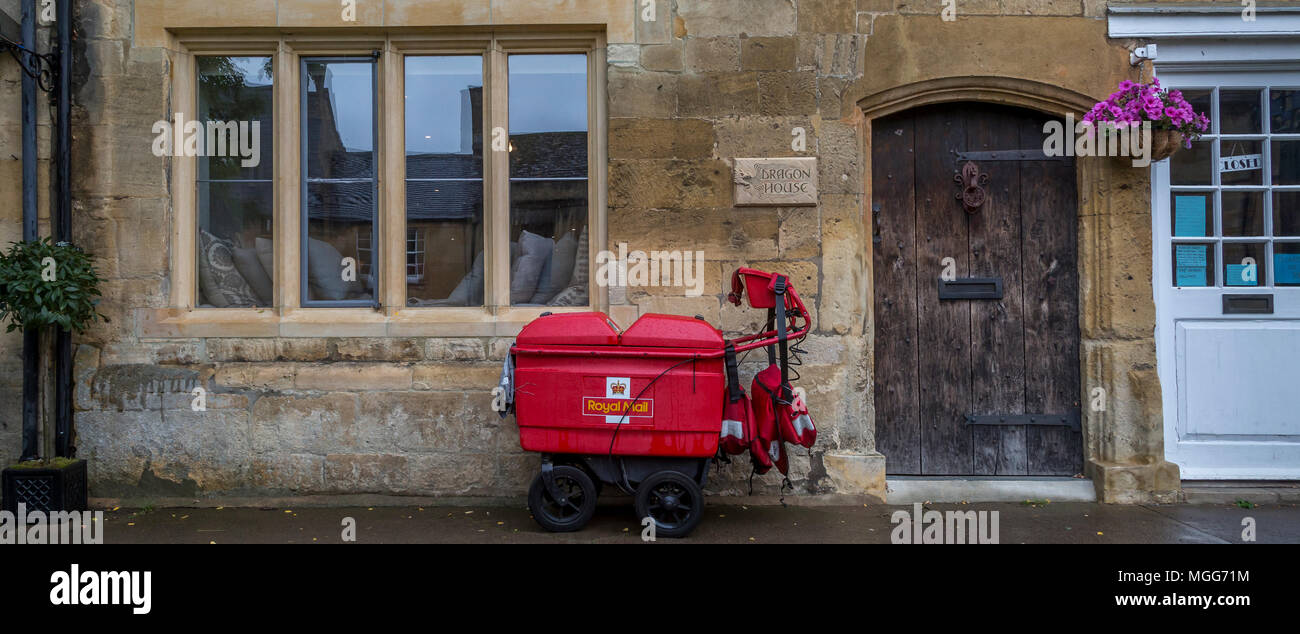 A Royal Mail trolley waits by the Cotswold limestone facade of the terraced Dragon House in the elegant market town high street of Chipping Campden - Stock Image