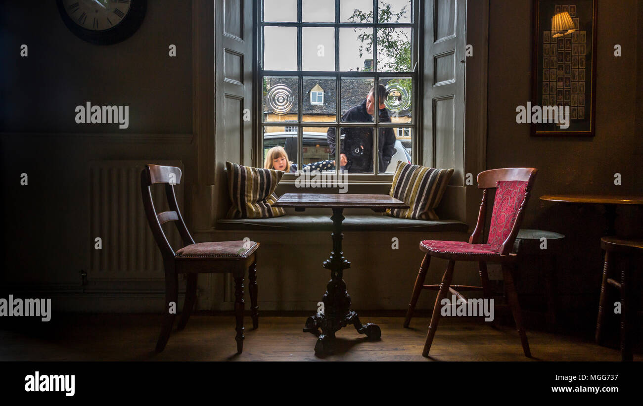 Open shuttered window lets the Cotswold's light spill onto the inviting antique table and chairs situated in The Bell Inn Moreton in Marsh Stock Photo