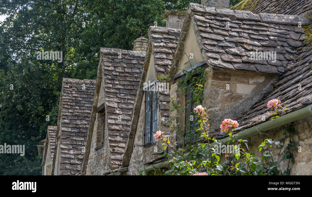 Bibury village's slate roofed row of dormers poke out of their Jacobean architecture Stock Photo