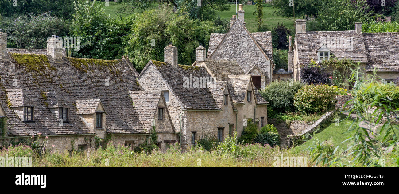 Bibury's classical Jacobean village showing Arlington Row stacked above the River Coln which attracts record breaking numbers of Japanese tourists - Stock Image