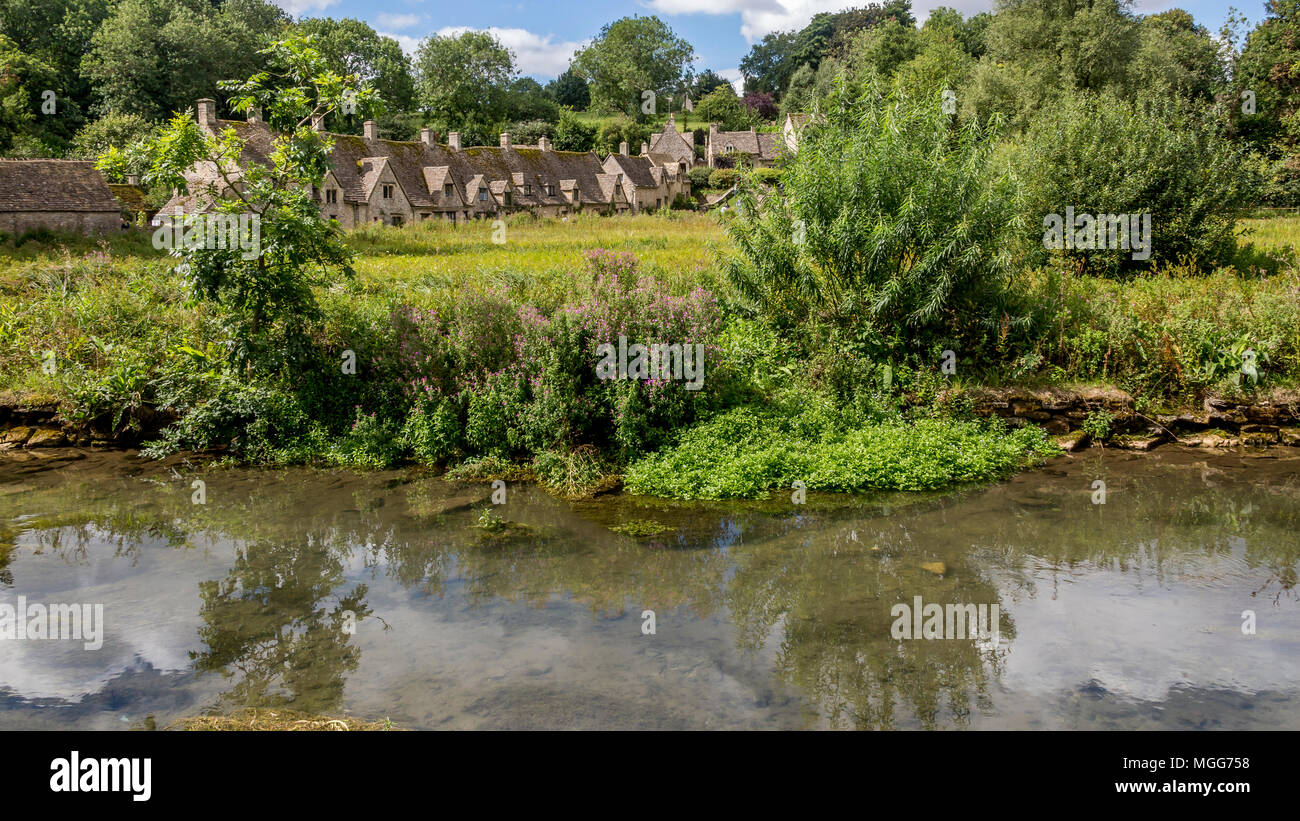 The River Coln flows through Bibury village's famous Arlington Row which is reflected in its calm waters Stock Photo
