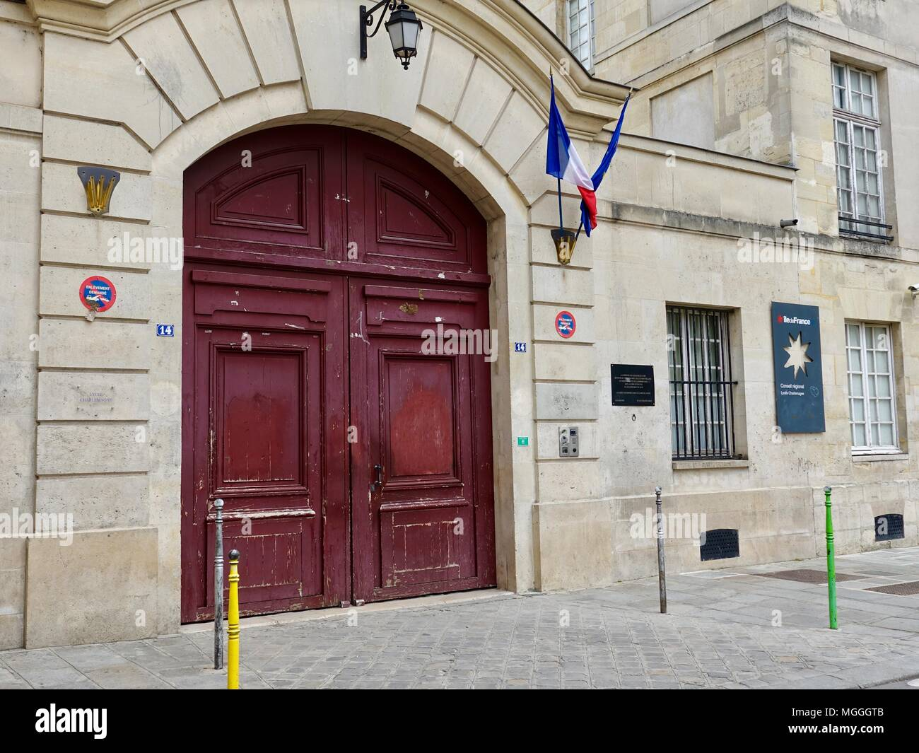 Red doors of the Lycée Charlemagne (French high school), located in the Marais, Paris, France. - Stock Image