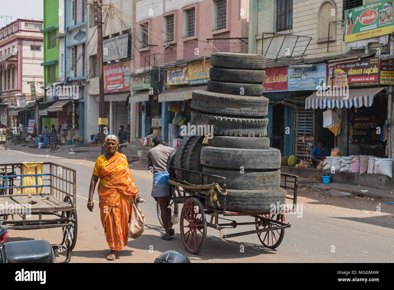 Madurai, India – March 9, 2018: Unidentified porter transporting a load of worn tires through the city centre - Stock Image