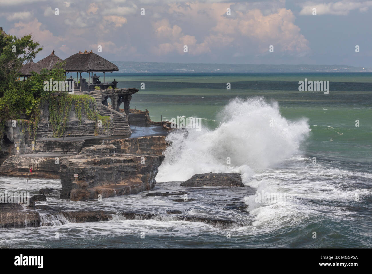 Waves crashing on Pura Tahah Lot sea temple on the Bali Sea, Indonesia - Stock Image