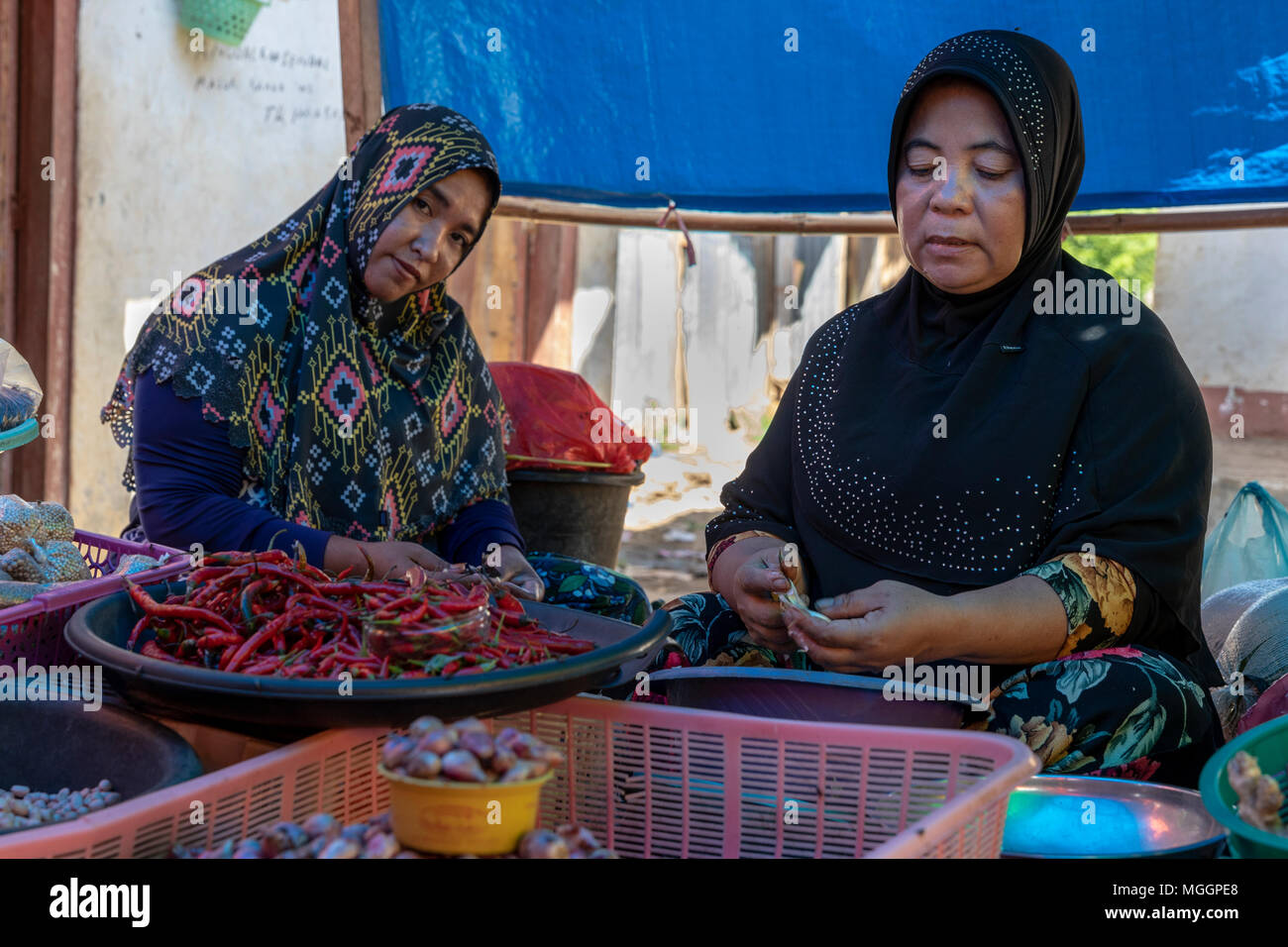 Two Muslim women selling hot peppers at Labuan Bajo food market, Indonesia - Stock Image