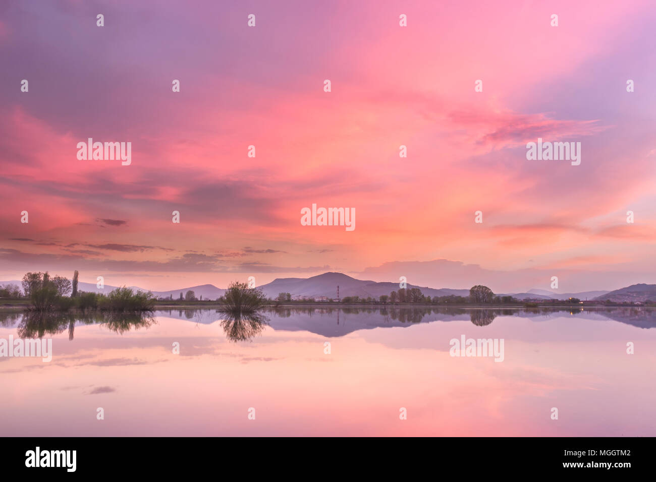 Burning Pirot cityscape sunset sky over artificial reflective lake and pink, orange fluffy clouds - Stock Image
