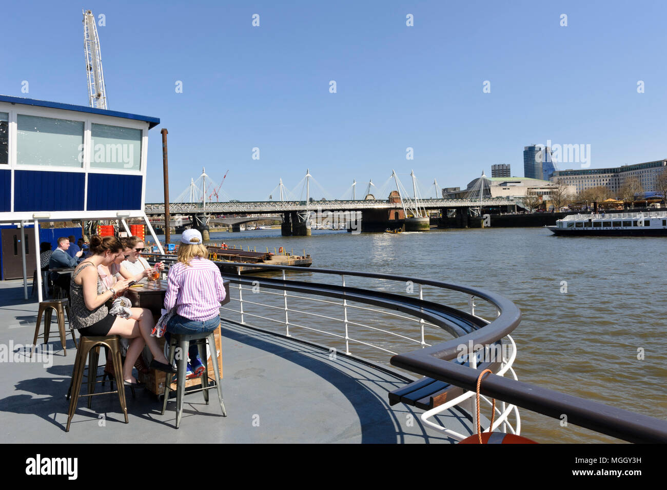 A group of people having drinks on a boat on the river Thames, London, England, United Kingdom Stock Photo