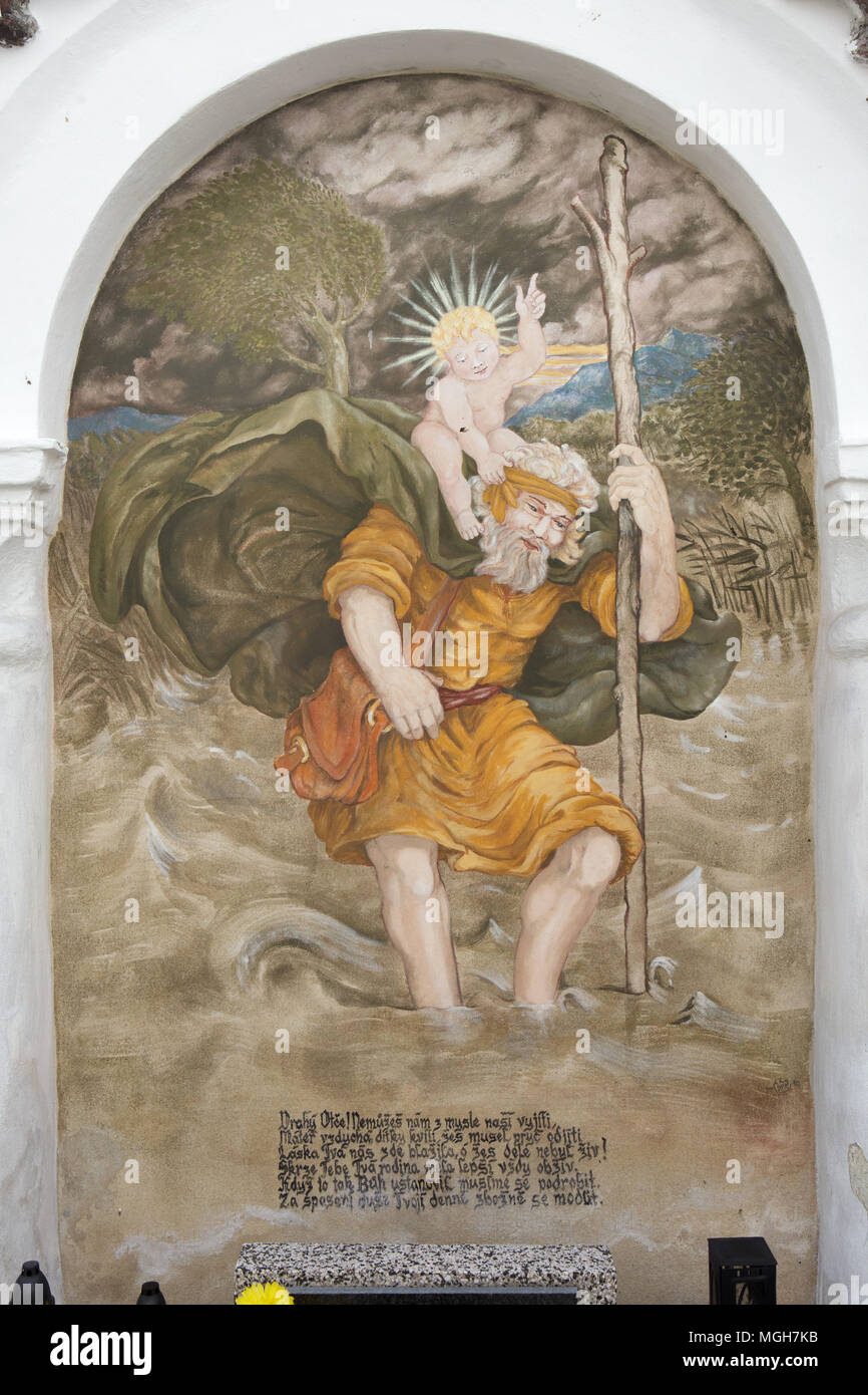 Saint Christopher carrying the Christ Child. Mural painting in the funeral chapel at the village cemetery in Albrechtice nad Vltavou in South Bohemian Region, Czech Republic. Funeral chapels placed on the cemetery wall were decorated with murals in the 1840s by local painter František Mikule conducted with parish priest Vít Cíza, who also composed poems for each mural. The murals were repainted several times during the 19th and 20th centuries and completely restored by the team led by Jitka Musilová in 2010-2013. Stock Photo