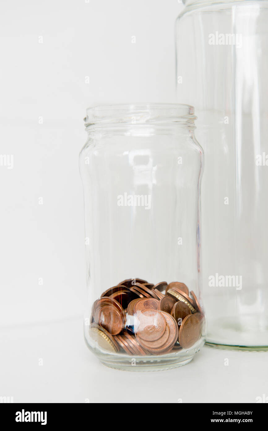 Concept of downsizing low funds using two jars of coins - Stock Image