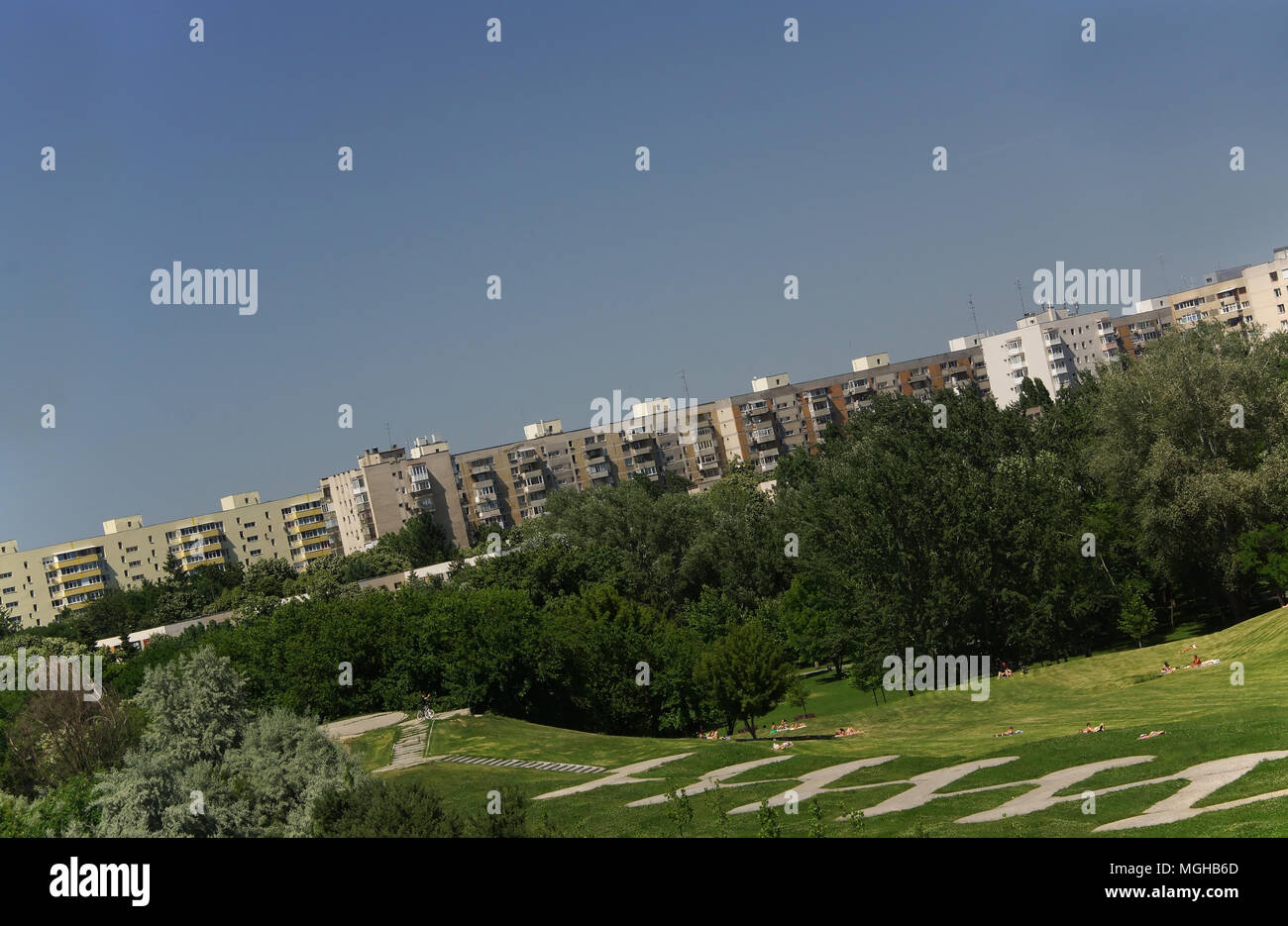 BUCHAREST,ROMANIA,JUNE 7,2015:dutch angle on Titan Park with distant people sunbathing on grass, apartments buildings skyline Stock Photo