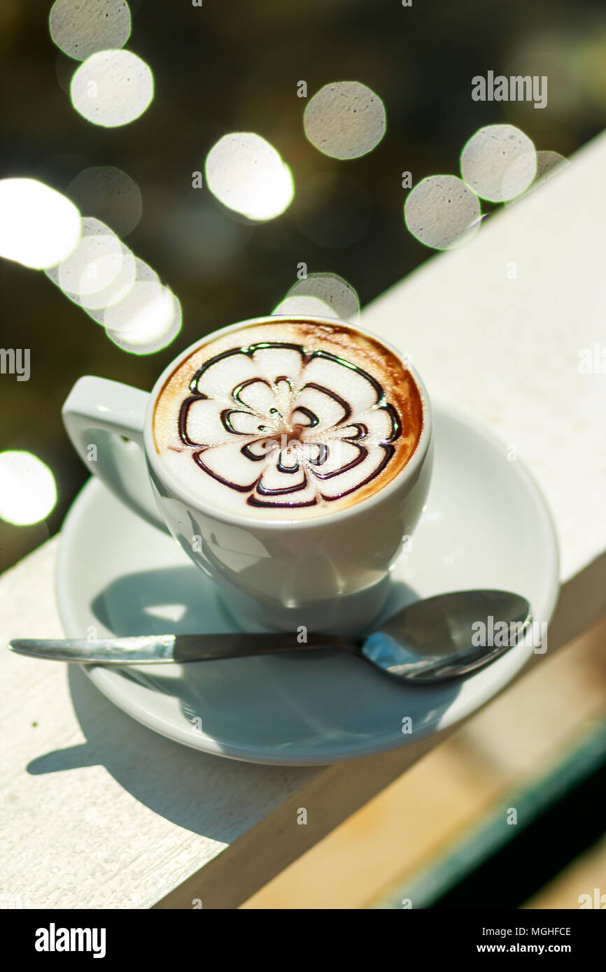 Hot coffee cappuccino in white cup.Morning coffee. white cup of latte hot coffee with leaf, flower pattern, latte art. Coffee Mug - Stock Image