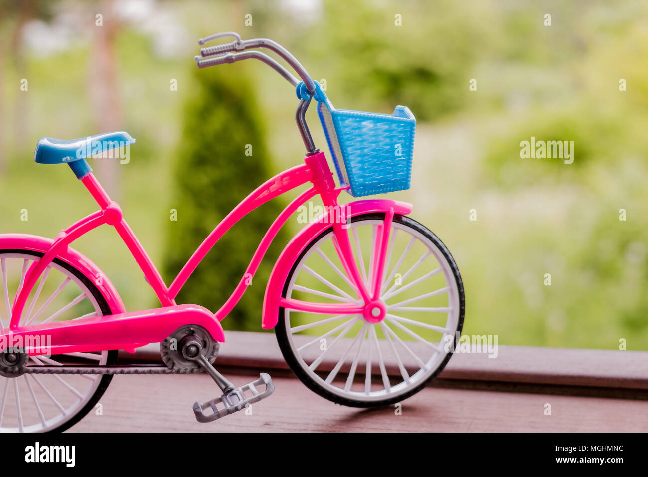 Small pink bicycle model on the handrail with garden background.Green transport.Vintage bicycle,selective and soft focus. Copy space - Stock Image