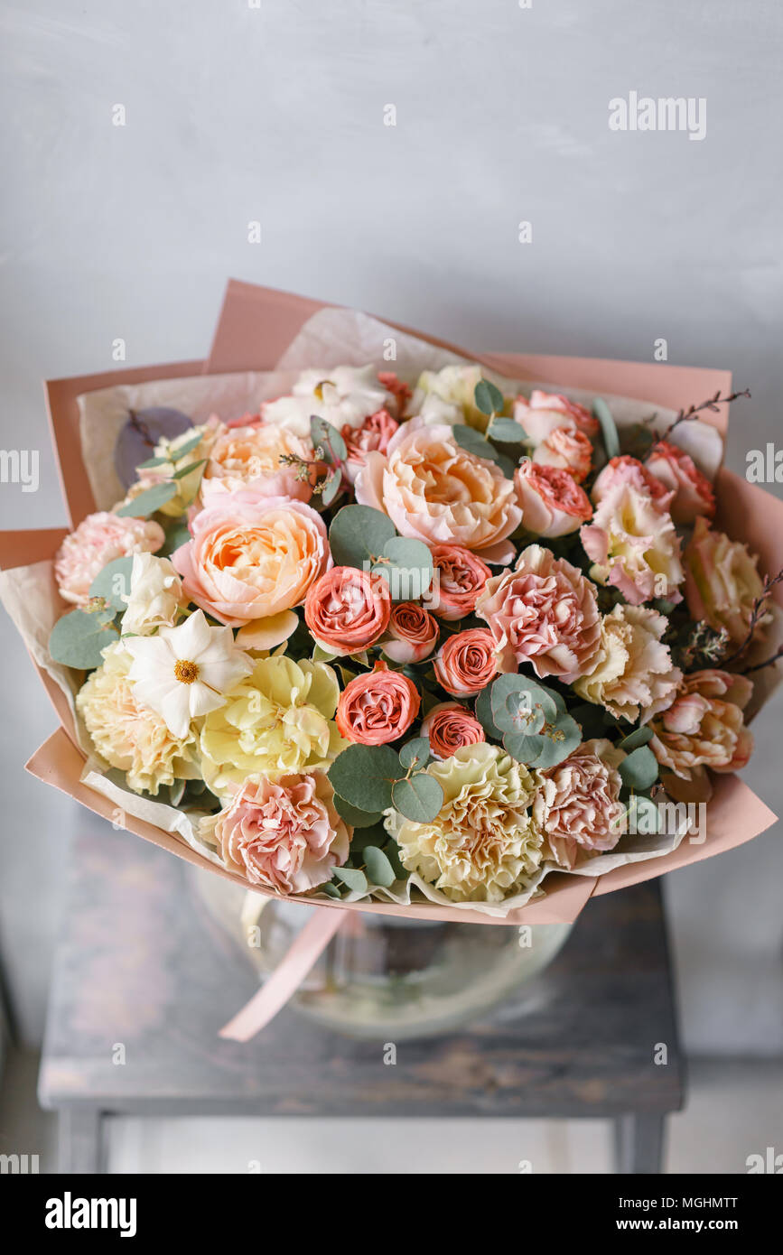 Pastel orange and pink bouquet of beautiful flowers on wooden table pastel orange and pink bouquet of beautiful flowers on wooden table floristry concept spring colors the work of the florist at a flower shop izmirmasajfo
