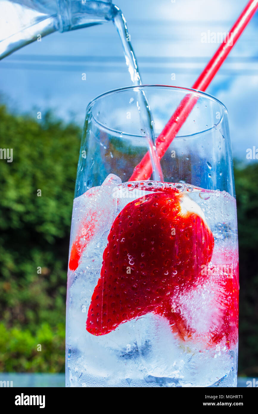 Strawberry drink is being poured from a jug into a glass with ice cubes and a straw on a garden table. Stock Photo