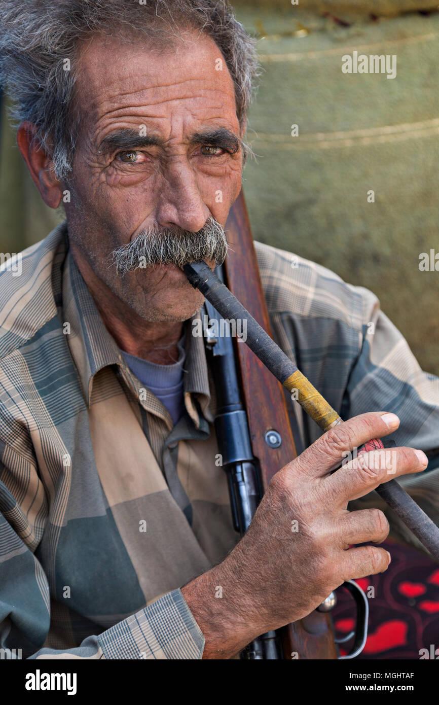 Iranian nomadic man belonging to the tribe known as Qashqai, smokes his pipe, in Firuzabad, Iran. - Stock Image