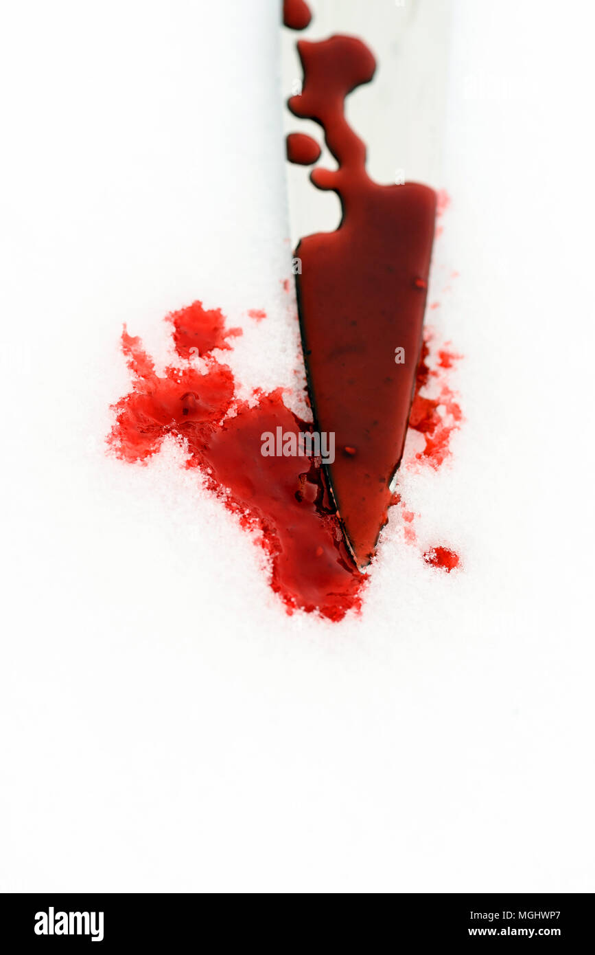 Sharp metal kitchen knife edge used as a violent murder weapon with blood drops on a white snow background. Blade covered in violence with copy space  Stock Photo